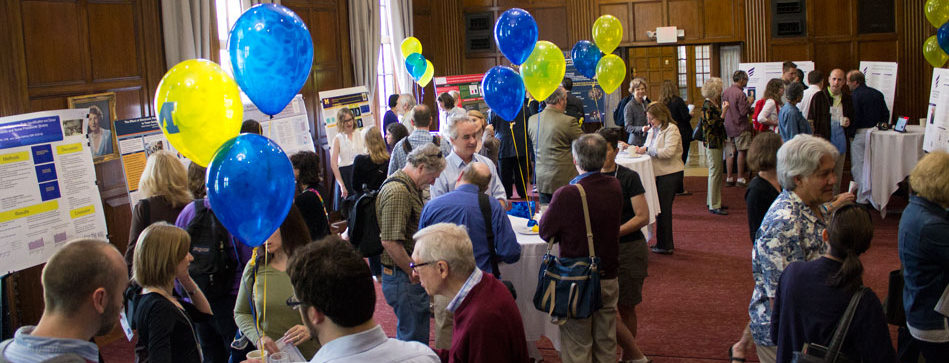 Poster fair with lots of people, blue and yellow balloons decorate the room