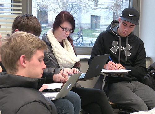 Photo of students taking notes on laptops and notebook
