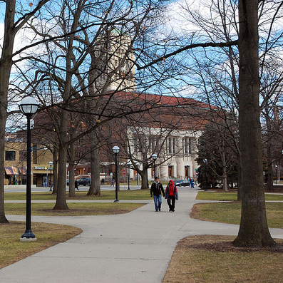 photo of 2 people walking with Hill Auditorium and the Bell Tower in the background